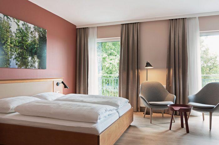 Extra lange Gesundheitsbetten sorgen für perfekten Schlafgenuss und eine großzügige Sitzecke bietet viel Komfort. Balkon mit Innblick